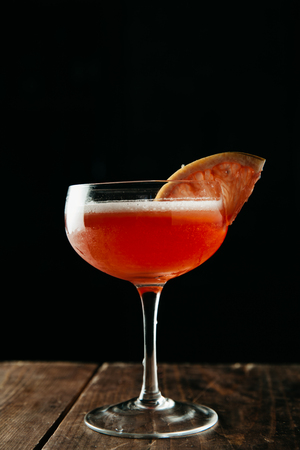 Pink cocktail garnished with a slice of blood orange on dark rustic background