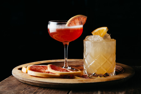 Two summer alcoholic drinks on dark rustic background