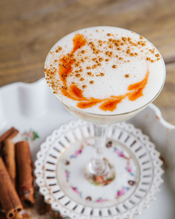 Foamed spicy fall cocktail garnished with cinnamon sticks on rustic background Stock Photo