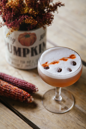 Pumpkin foamed cocktail garnished with coffee beans on rustic background