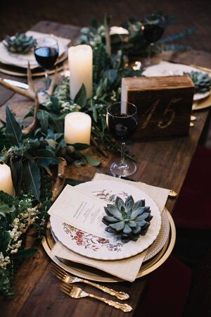 Rustic wedding table seting with vintage plates, green and white eucalyptus garland, deer antlers, gold utensils. Boho style. Table set for an event, party, date or wedding. Red wine served