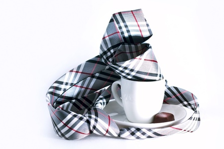 bussiness man: Checkered necktie lie on the table twisted around a cup of coffee  A little chocolate candy lie in the white ceramic saucer near ceramic cup  Objects are isolated; background is white