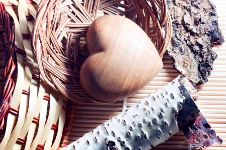 Different kinds of wood   birch, pine, maple, ash, nut  on the bamboo mat  Heart of wood is in a  wicker basket  Two wicker baskets made of vine and willow on the table  photo