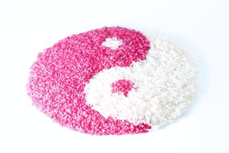 taoisme: De zaden van basmati rijst liggen op de tafel in de vorm van Yin Yang simbol van het taoïsme De kleur van een deel van rijst is wit, hieronder stapsgewijs een is magenta geïsoleerde objecten op een witte achtergrond