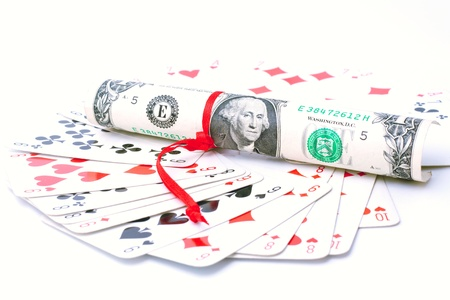 A deck of playing cards and one dollar bill twisted up in a tube and bandaged  with a red ribbon on white background  Numbers of playing cards are  nine, eight,six, ten ;  suits of cards are   spades, hearts, clubs, diamonds   photo