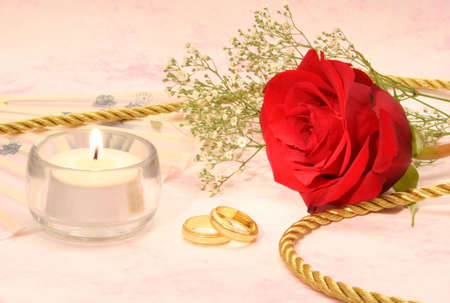 Rose with Gold Wedding Bands and Candle on Pink Background