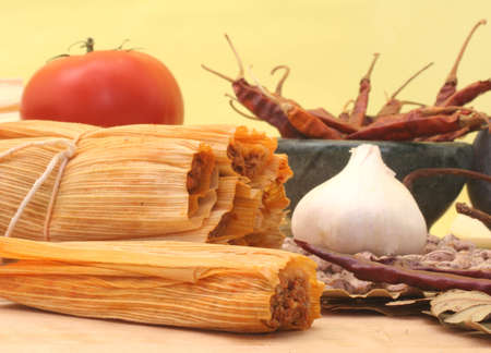 Tamales With Garlic, Beans and Tomato on Yellow Background Stock Photo