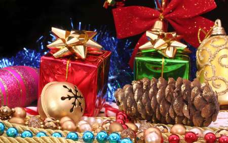 Christmas Gifts With Beads and Pine Cone on Black Background