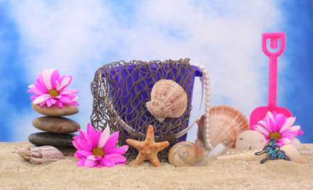 Sand Pail With Net and Sea Shells on Sand With Blue and White Background Stock Photo