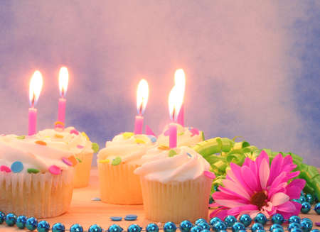 Flowers and Cupcakes with Candles on Blue Sky Background