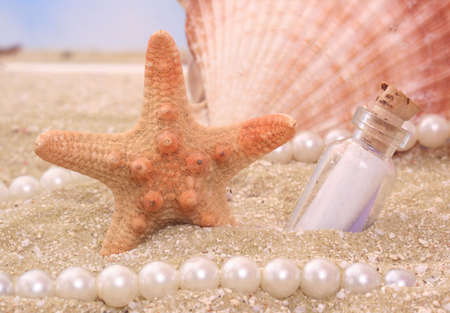 Starfish With Bottle on Sand With Pearls and Shell Stock Photo