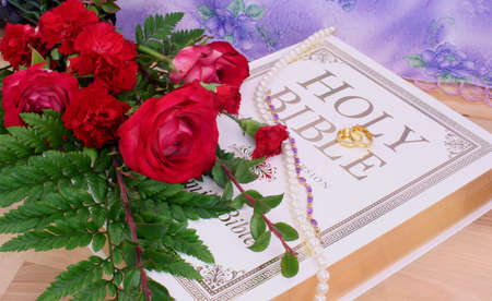 Roses With Bible and Wedding Rings on Wood Table