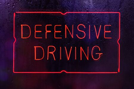 Neon Defensive Driving Sign in Wet Window