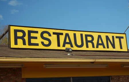 Restaurant Sign Outdoors On Building Roof With Blue Sky Foto de archivo