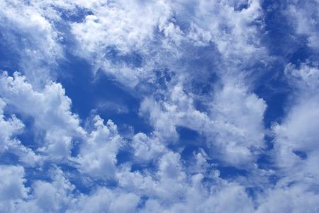 Wild cumulus clouds in the clear deep blue sky