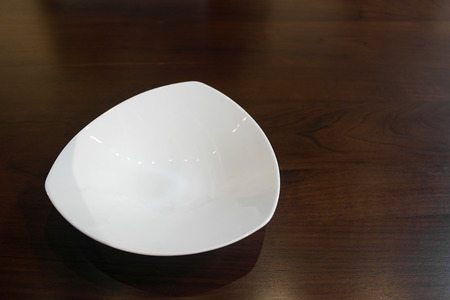 polished: Expensive triangular shaped luxury porcelain plate on an oak table setting