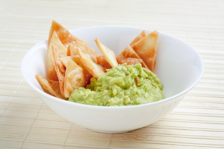 White bowl with guacamole and homemade nachos Stock Photo