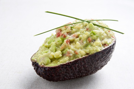 Avocado stuffed with guacamole decorated with chives Stock Photo