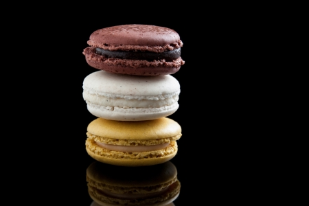 macaroon: chocolate macaroons, vanilla and caramel isolated on black