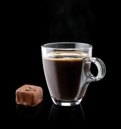 cafe bombon: taza de caf� con un bomb�n de chocolate en el fondo negro