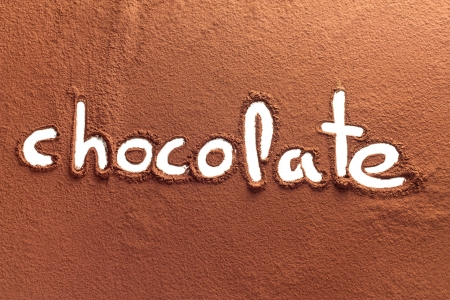 The word chocolate written on cocoa powder photo