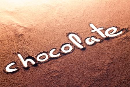 cocoa powder: The word chocolate written on cocoa powder Stock Photo