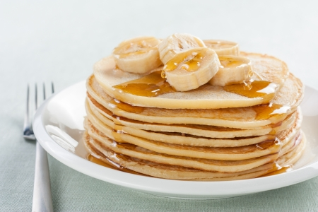 hotcakes: pancakes with banana and syrup on white plate
