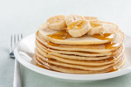 palatschinken: Pfannkuchen mit Banane und Sirup auf wei�em Teller