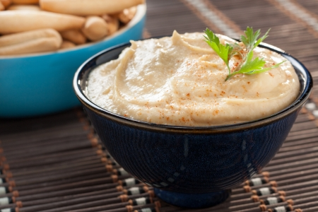 bowl of hummus with parsley and bread sticks Stock Photo