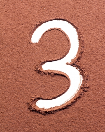 Number 3 made of cocoa powder on white background photo