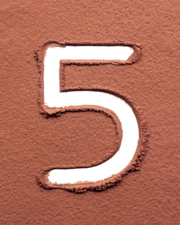 Number 5 made of cocoa powder on white background photo