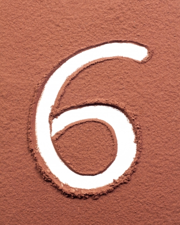 Number 6 made of cocoa powder on white background photo