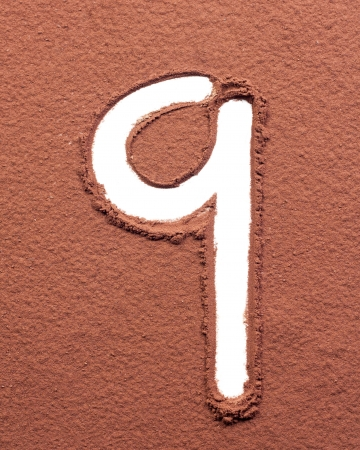 Number 9 made of cocoa powder on white background photo