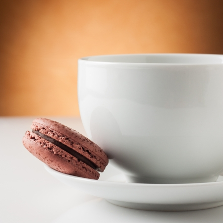Cup of coffee with a delicious chocolate macaron photo