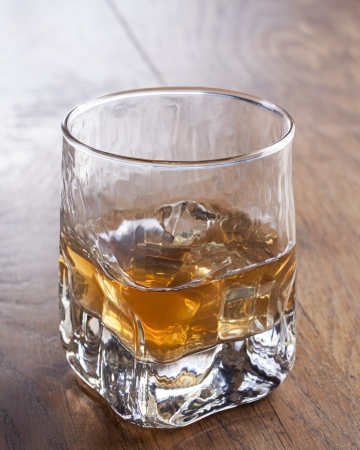 Glass of whiskey with ice on wooden table Stock Photo - 17083926