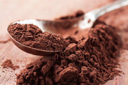 Brown chocolate powder on a spoon over a wooden table