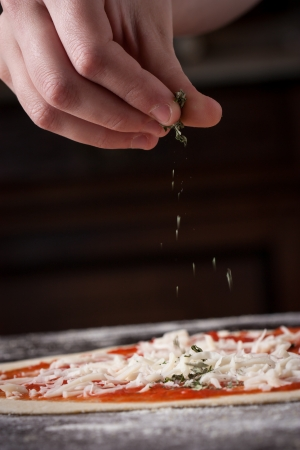 Cook putting oregano over mozzarella and tomato on a raw pizza close-up photo