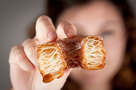 Croissant and doughnut mixture being held by a girl close-up photo