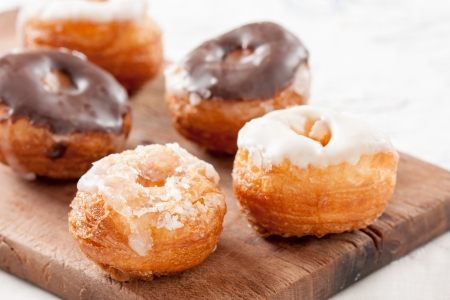 Mini croissant and doughnut mixture assortment on wooden table photo