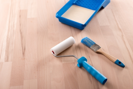 paintroller: Paint-roller and brush on wooden table ready to paint
