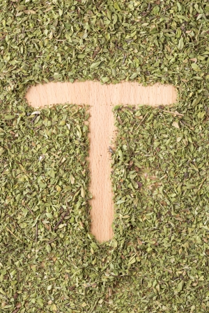 Letter T written with oregano on wooden table photo