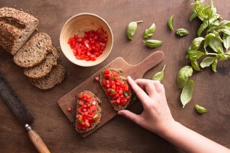 Holding Italian bruschetta on wooden table overview Stock Photo - 21634841