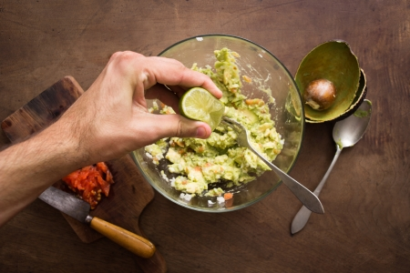 squeezing: Squeezing lime on guacamole mix overview Stock Photo