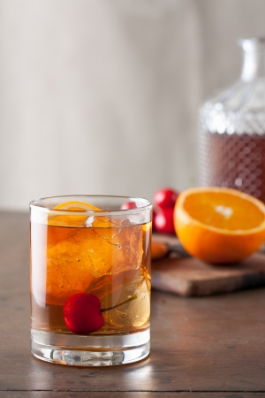 Classic old-fashioned cocktail with a cherry on a wooden table Stock Photo
