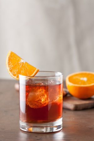 Classic negroni cocktail with an orange slice on wooden table photo