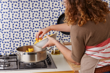 Young woman pouring vegetables on a pan toprepare cream photo