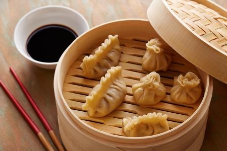 Homemade dim-sum asian dumplings on a traditional bamboo steamer Stock Photo
