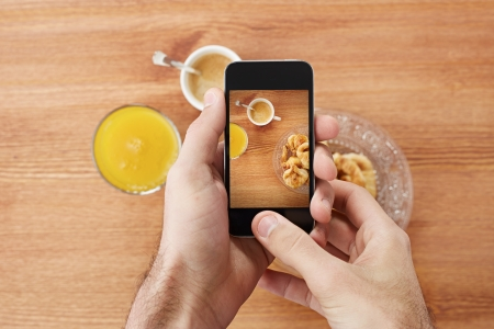 Hands taking photo of breakfast including croissants, cofee and orange juice with smartphone photo