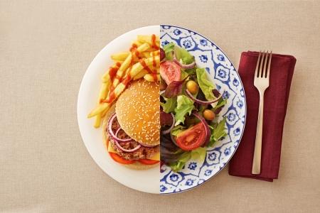 Low fat healthy salad against unhealthy greasy burger