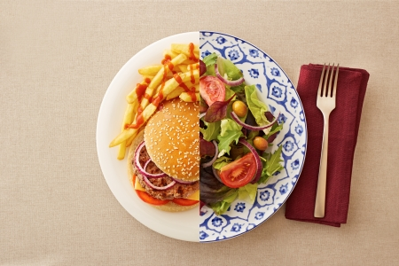 calory: Low fat healthy salad against unhealthy greasy burger